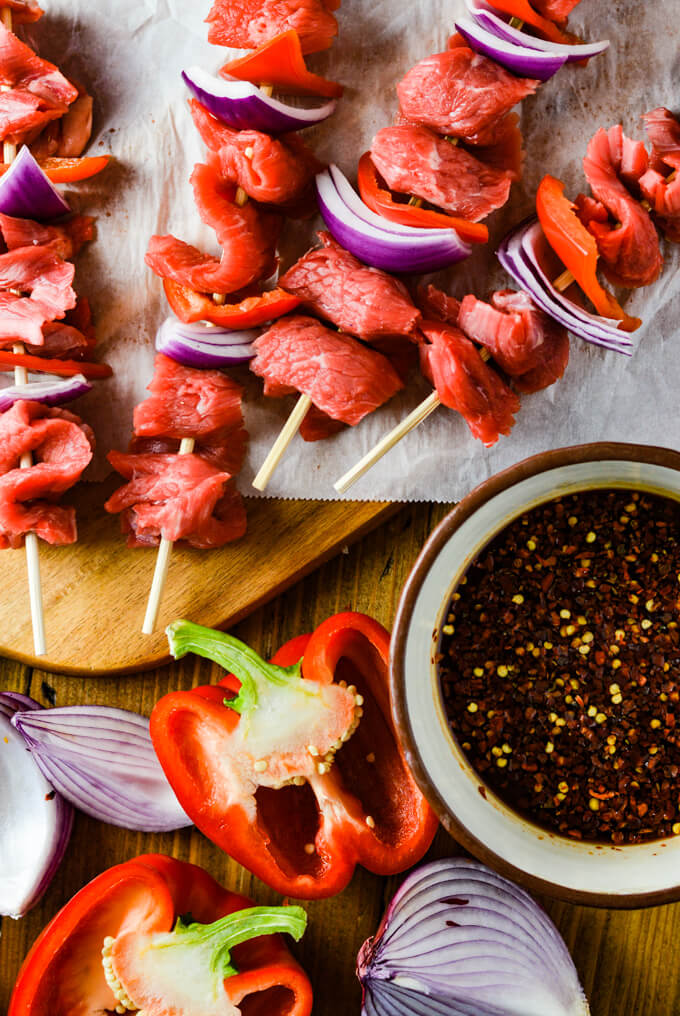 Raw flank stead, red onions and red bell peppers on four wooden skewers laying on a wooden cutting board with parchment paper. A bowl of marinade and halved red onions and red bell peppers sit next to it.