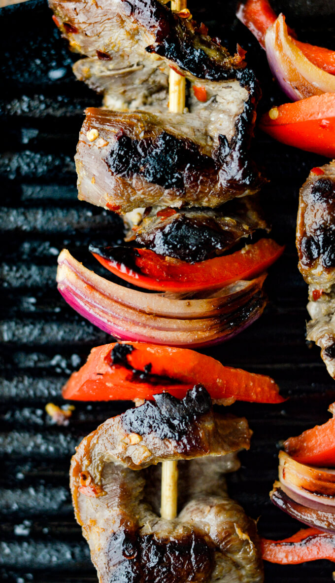 Beef Satay - A closeup view of flank steak, red onions, red bell peppers on wooden skewers are on an Electric Grill.