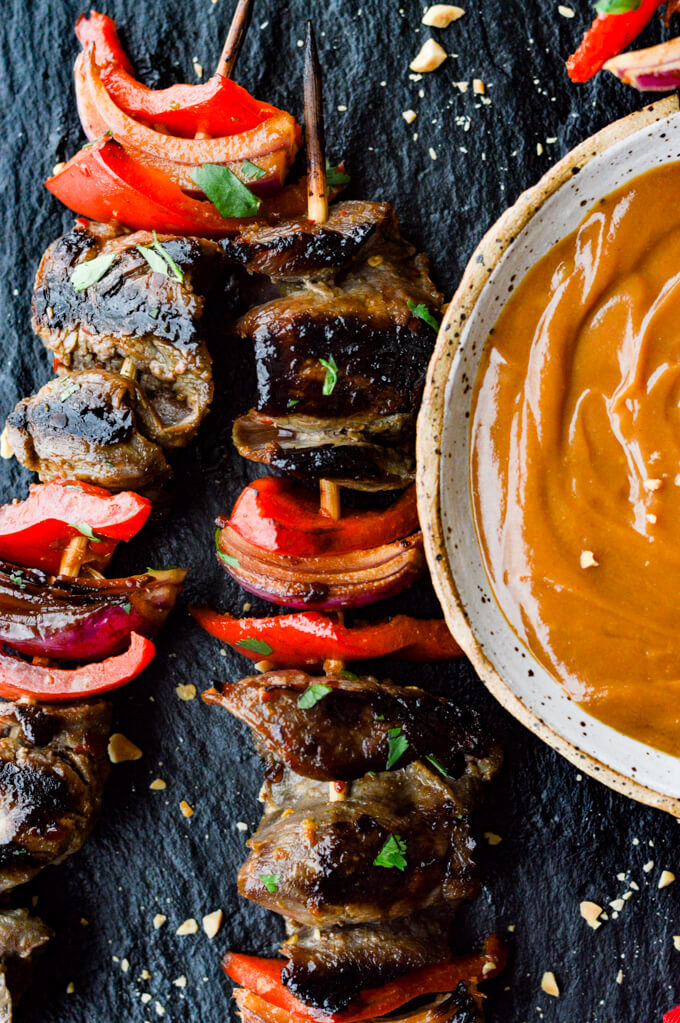 Beef Satay - Flank steak, red onions and red bell peppers on wooden skewers with a bowl of peanut sauce next to them.