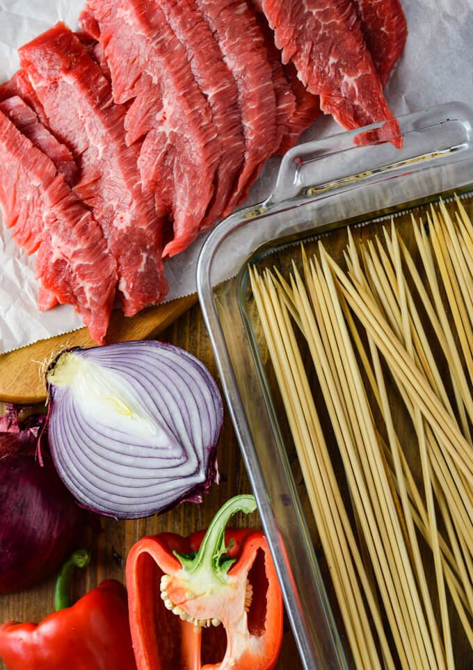Strips of raw flank steak with wooden skewers in a glassware pan of water. Halved red onion and red bell pepper sit next to it.