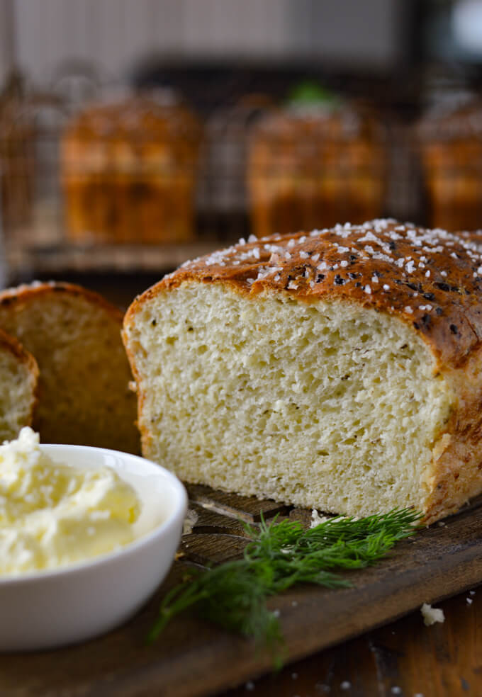 A cut loaf of dill bread with a small white bowl of butter sitting in front of it.