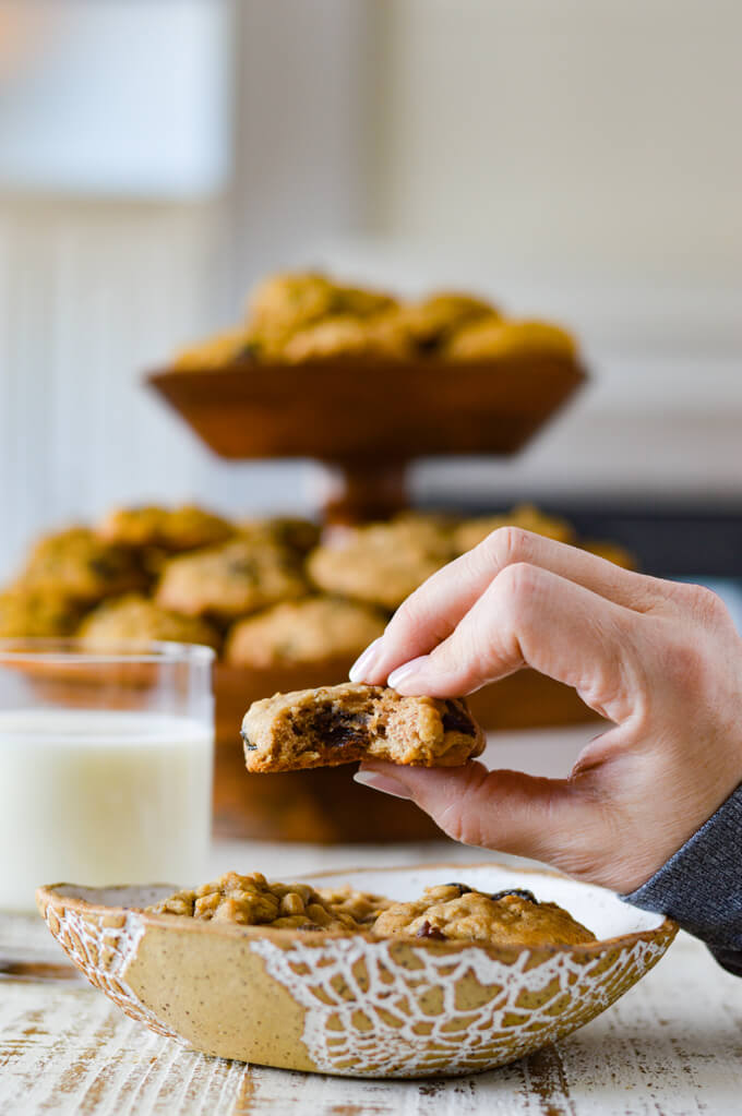 A bowl of oatmeal raisin cookies with a hand holding one with a bite out of it. A glass of milk and a bunch of cookies sit in the background.