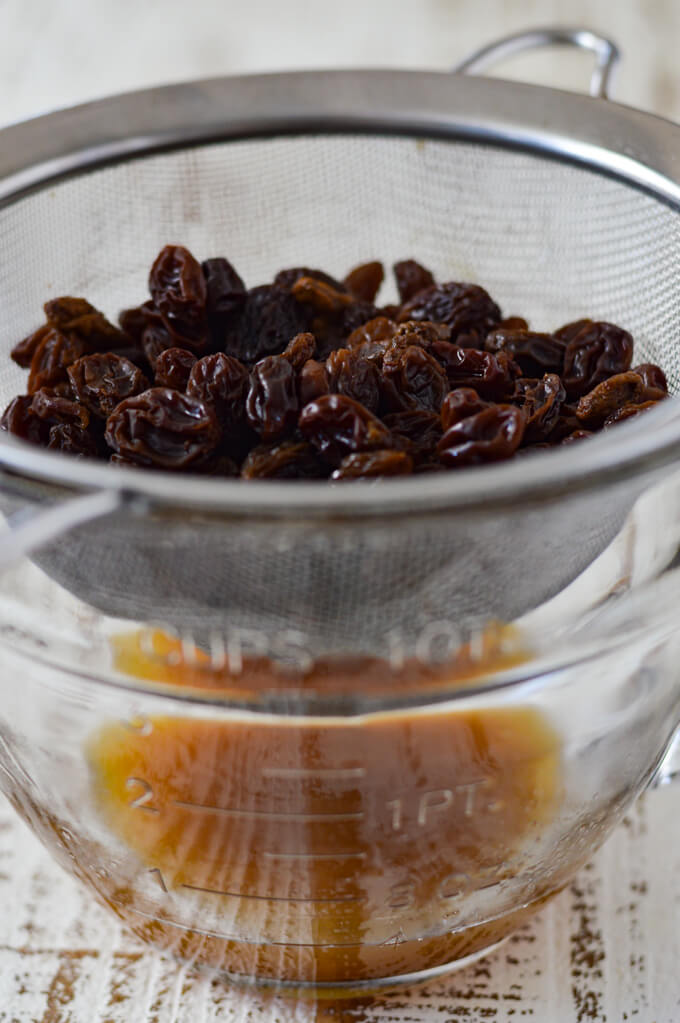 Boiled raisins draining in a wire strainer into a clear measuring cup.