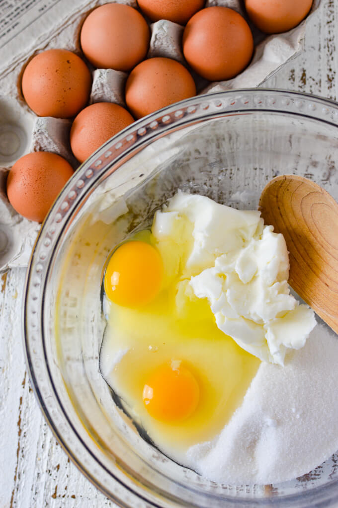 A bowl of shortening, sugar and two cracked eggs with a wooden spoon. A carton of eggs sit next to the bowl.