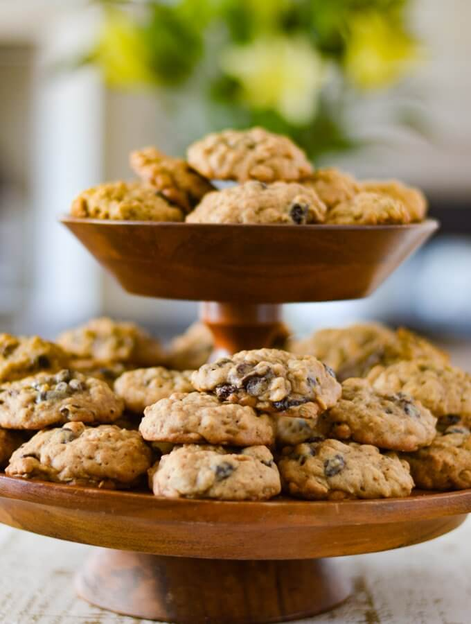 A tiered wooden platter full of oatmeal raisin cookies with a bouquet of flowers blurred in the background.