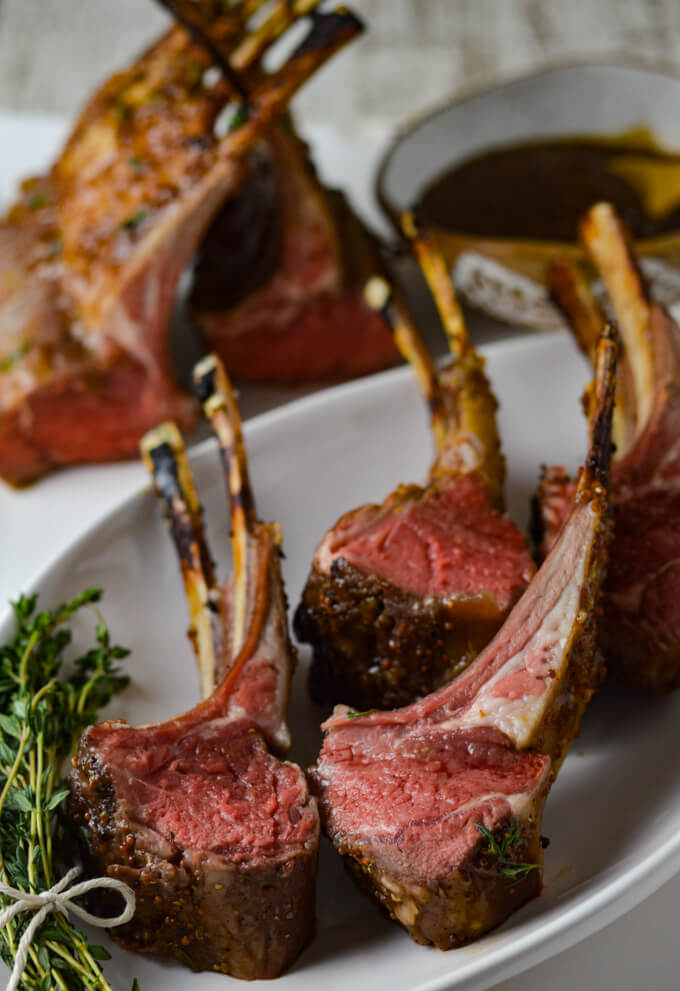 Four lamb chops cooked rare sitting on a white plate with a bundle of thyme next to it. Two partial racks of lambs are in the background with a bowl of apricot mustard sauce.