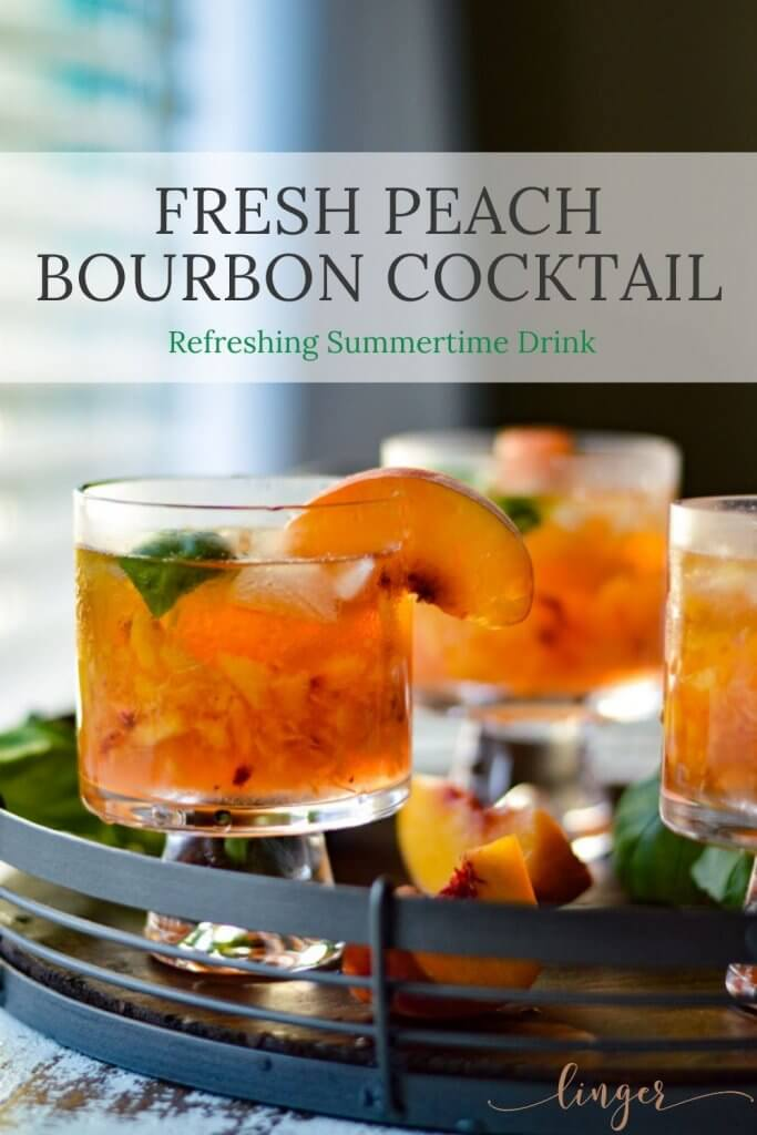 A tray of peach bourbon cocktails with fresh peach slices and fresh basil scattered around.