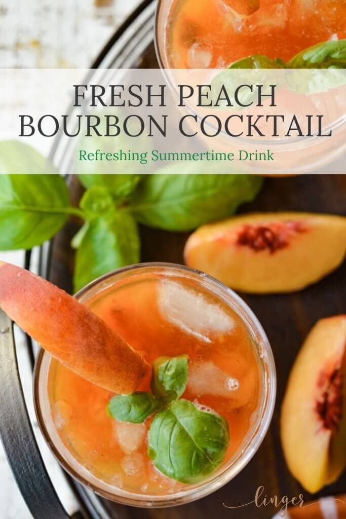 Two peach bourbon cocktails on a round wooden tray with fresh peaches and fresh basil.