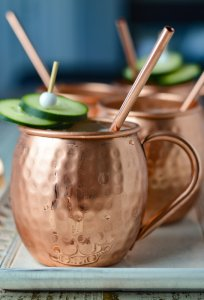 A cucumber Moscow Mule in a copper mug with three more mugs in the background. A copper straw is sticking out of all three cocktails and cucumber slices as a garnishment.