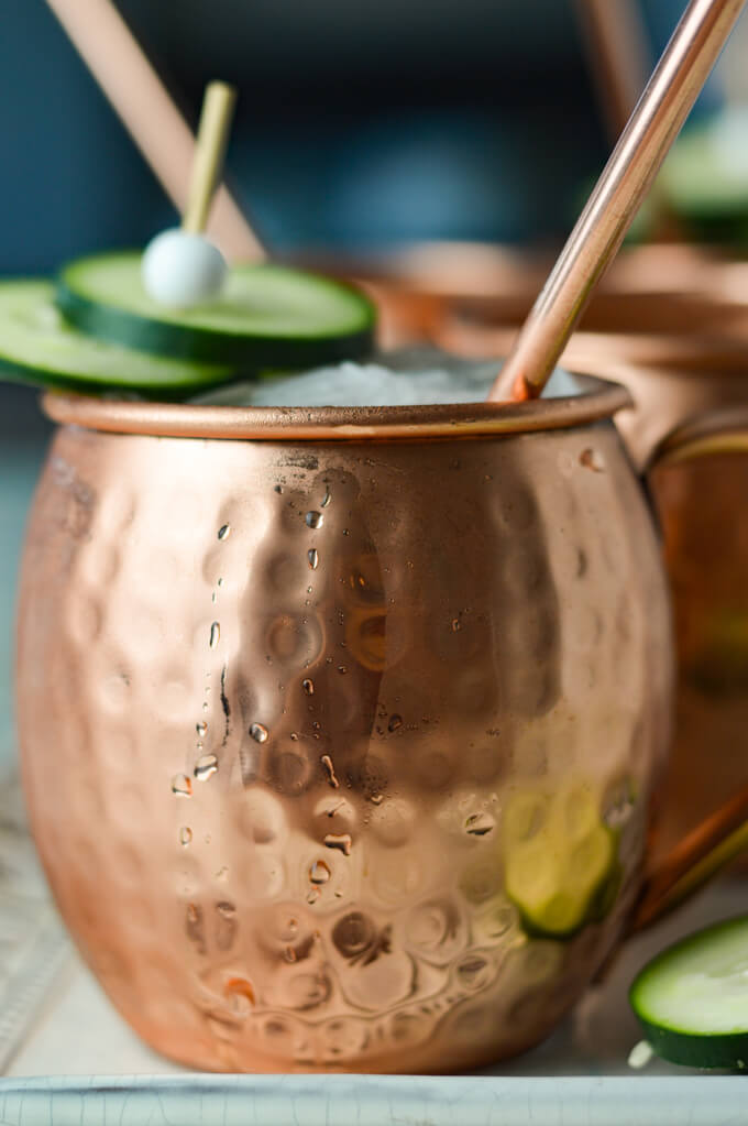 A close-up photo of a moscow mule in a copper mug with a straw and cucumber slices as a garnishment.