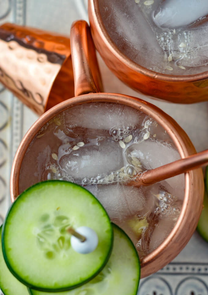 A close-up photo of a top view of a couple moscow mules in copper mugs with copper straws, a copper shot glass and sliced cucumbers as a garnishment.