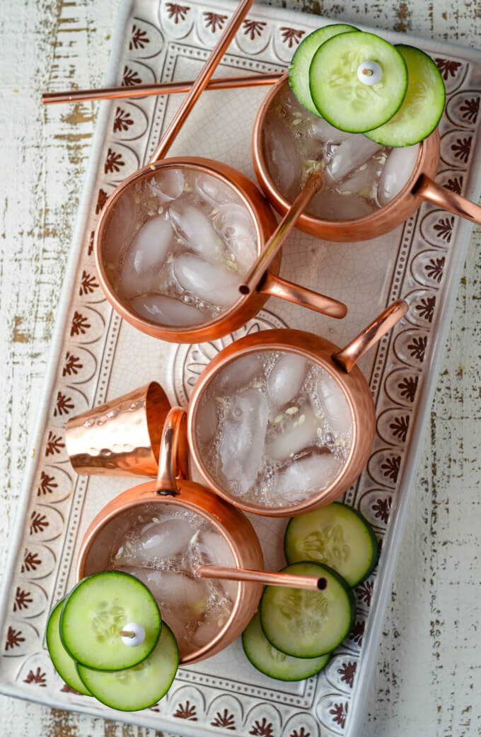 A white serving tray with 4 moscow mules sitting on it. These are in copper mugs with copper straws and a copper shot glass. Cucumber slices are garnishments.