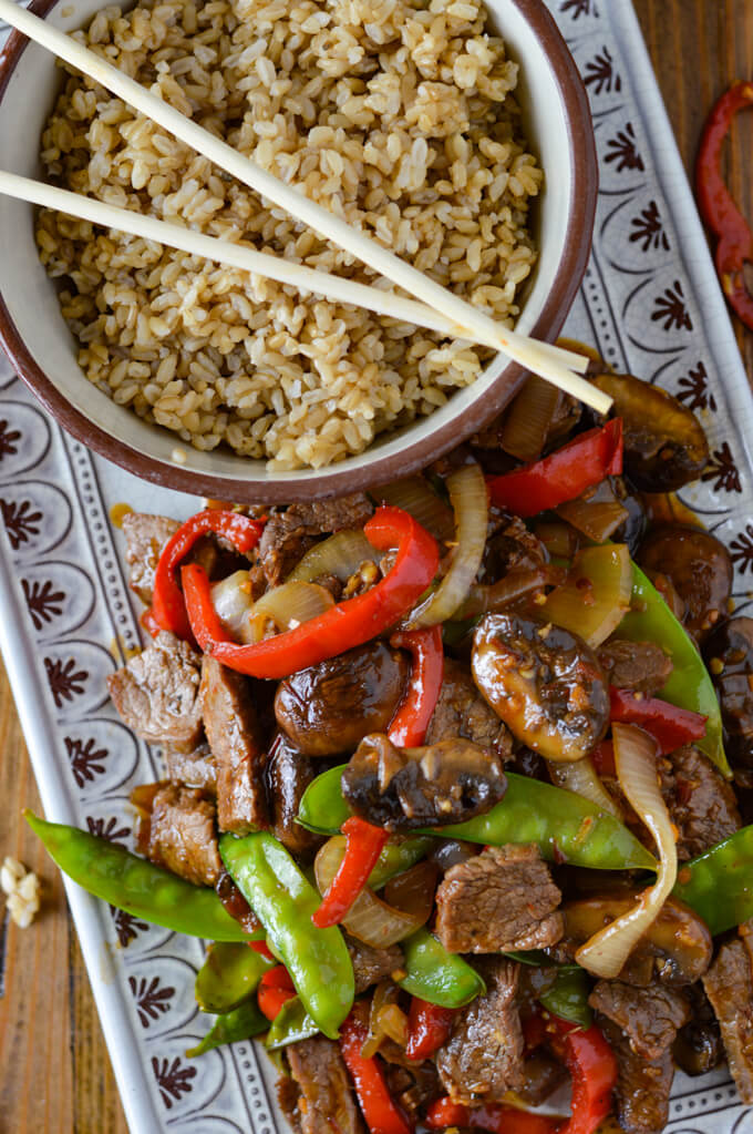 A serving platter of flank steak stir fry next to a bowl of brown rice and wooden chop sticks.