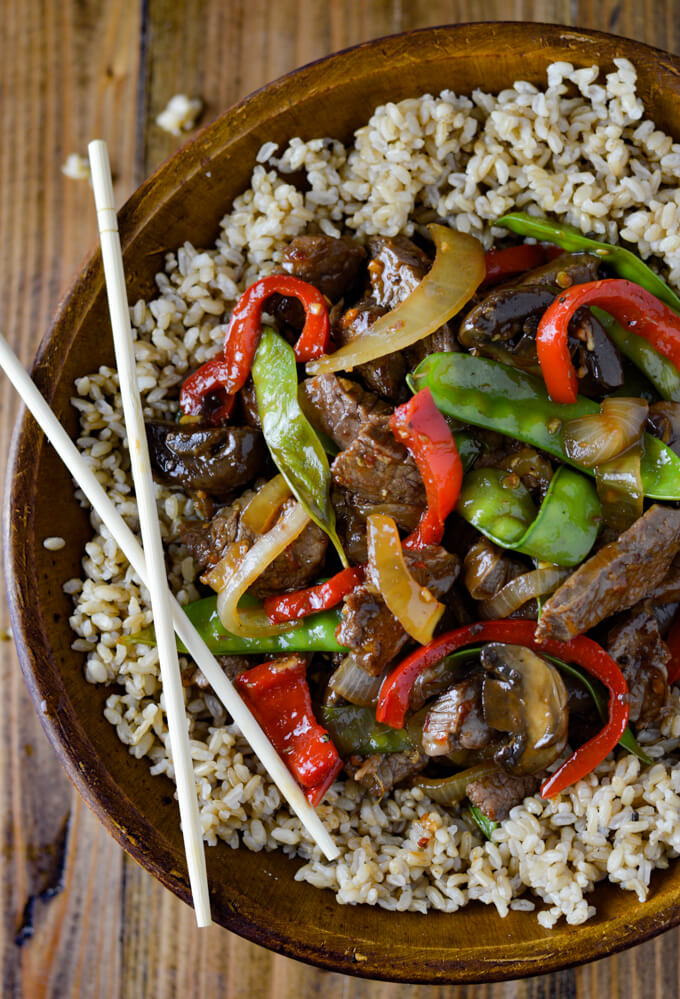 A wooden bowl of brown rice and flank steak stir fry. A pair of wooden chop sticks rests on the bowl.