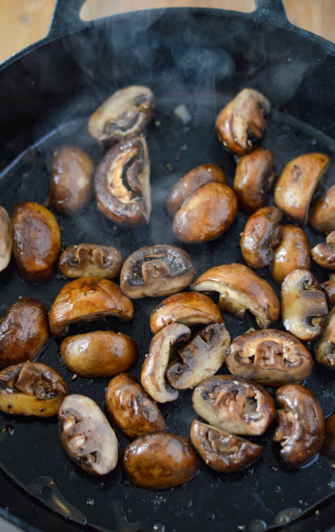 A cast iron skillet of sautéed mushrooms.