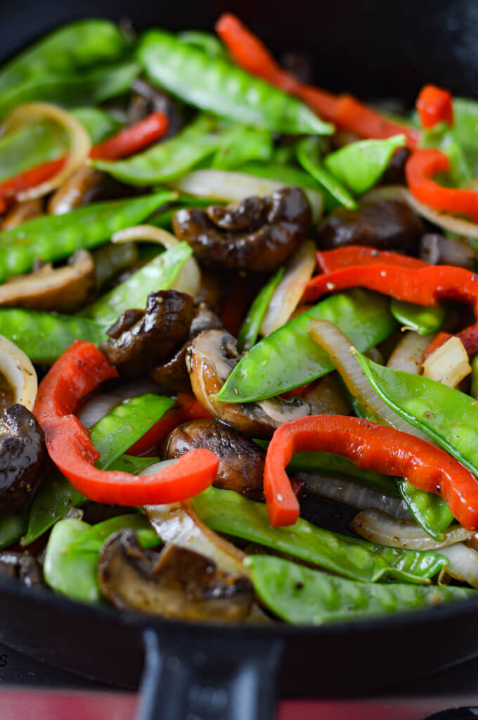 A pan of sautéed red peppers, onions, mushrooms and snow peas.