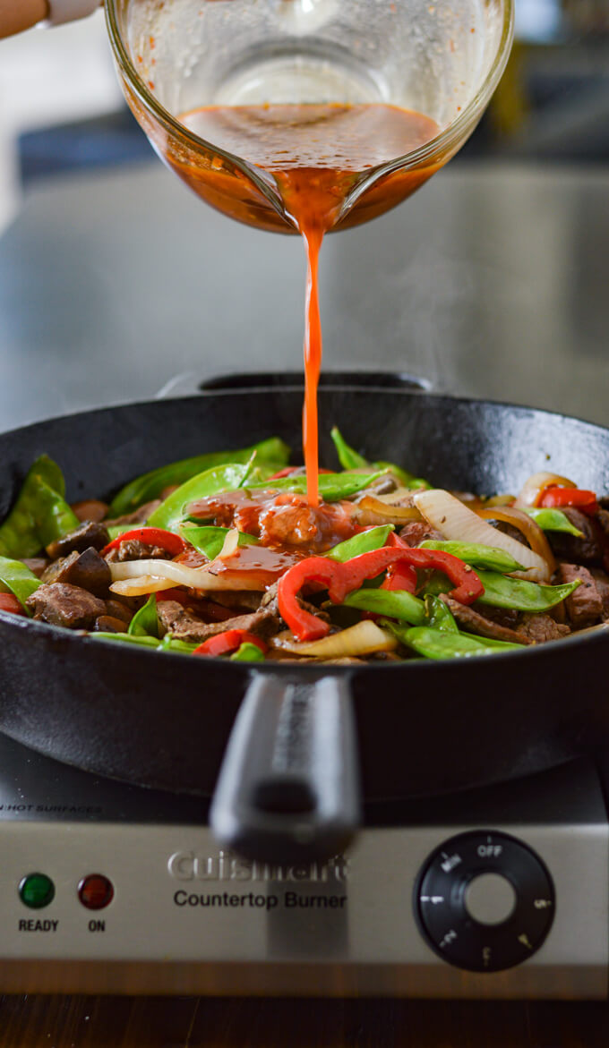 A pan of sautéed vegetables with a glass measuring cup pouring out a chili garlic sauce over the vegetables.