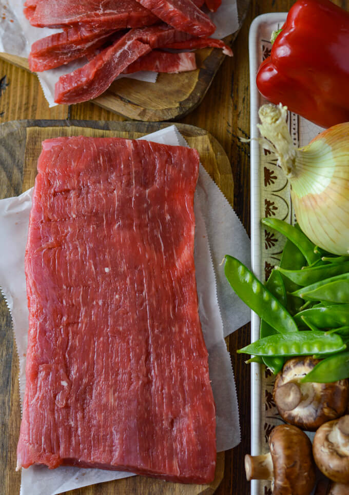 A slab of raw flank steak on a wooden cutting board next to strips of flank steak on another cutting board. A platter of raw red peppers, onions, snow peas and mushrooms sit next to the steak.