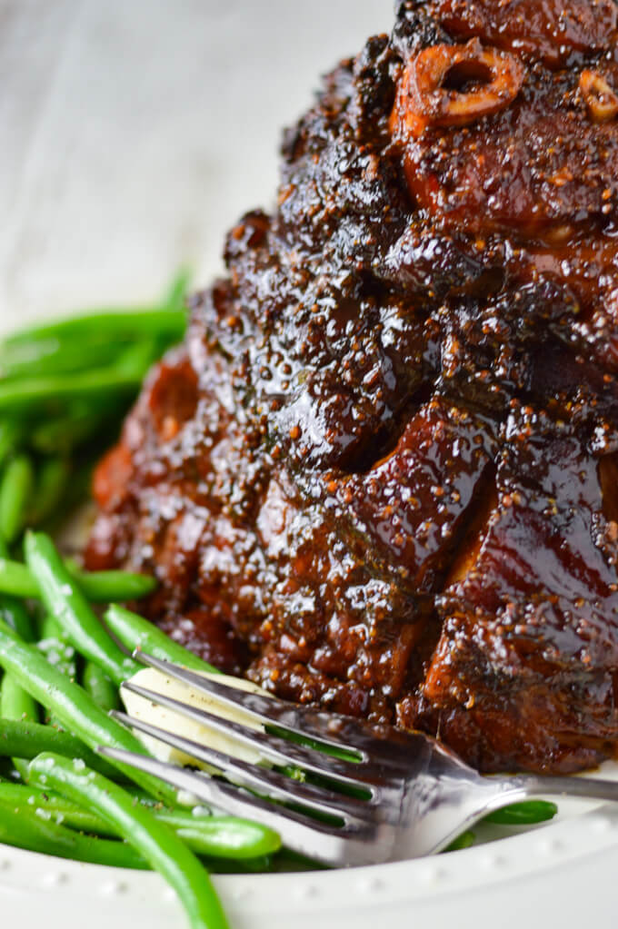 A close-up view of a cooked glazed ham sitting on a white platter, a large serving fork sits next to it along with a side of green beans.