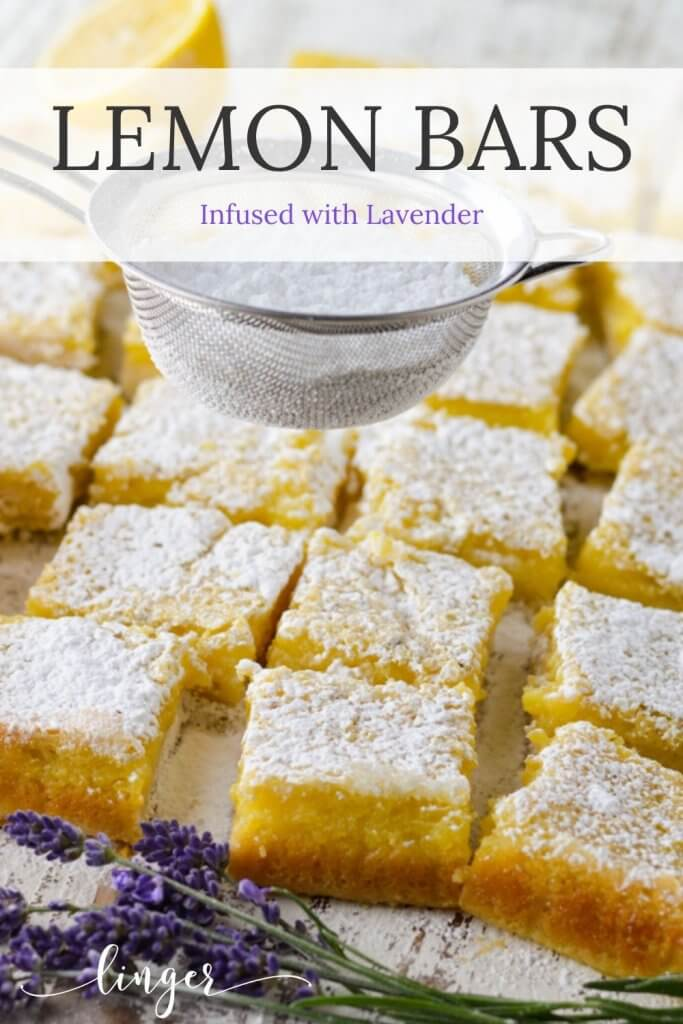 Cut lavender infused lemon bars with a metal sieve of powdered sugar above it. Sprigs of lavender sit in front of it.