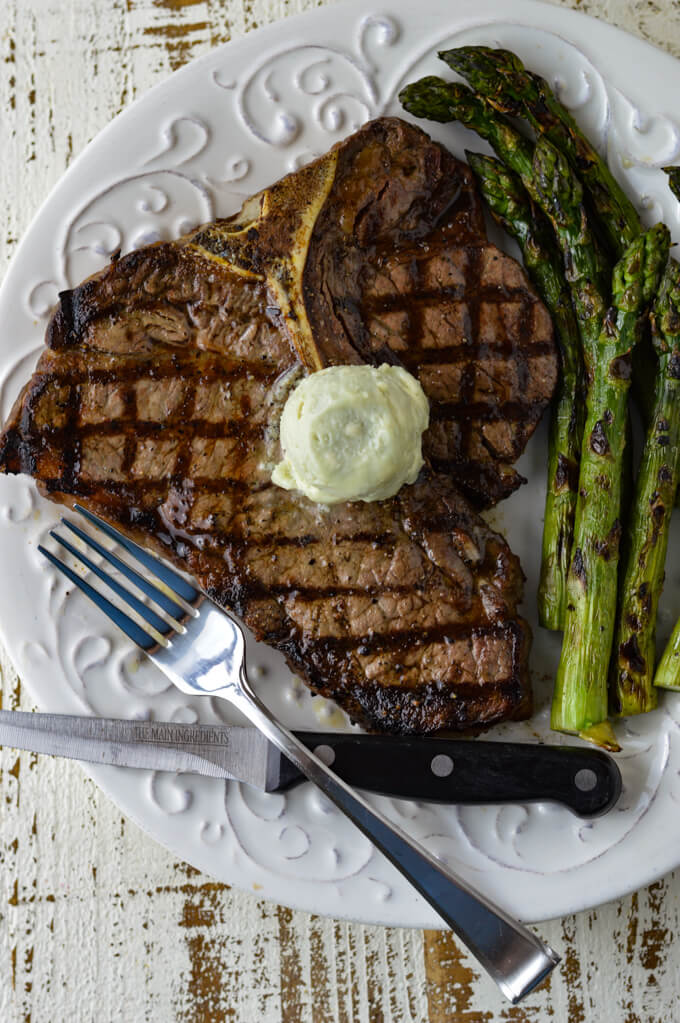 A grilled t-bone steak on a white plate with a round of blue-cheese butter melting on top. A fork and a steak knife sit in front and grilled asparagus is on the plate next to the steak.