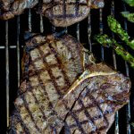 Two cooked t-bone steaks are on the grill with crisscross grill marks on them. Asparagus sits next to them on the grill.
