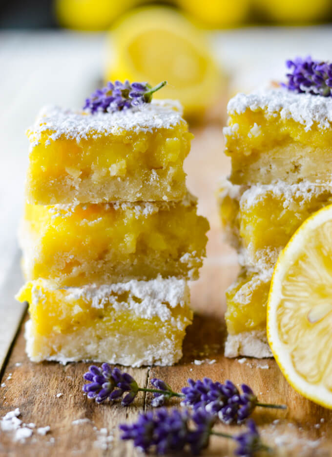 A stack of lavender infused lemon bars sit on a wooden tray . They are sprinkled with powdered sugar and have a fresh lavender sprig on top.