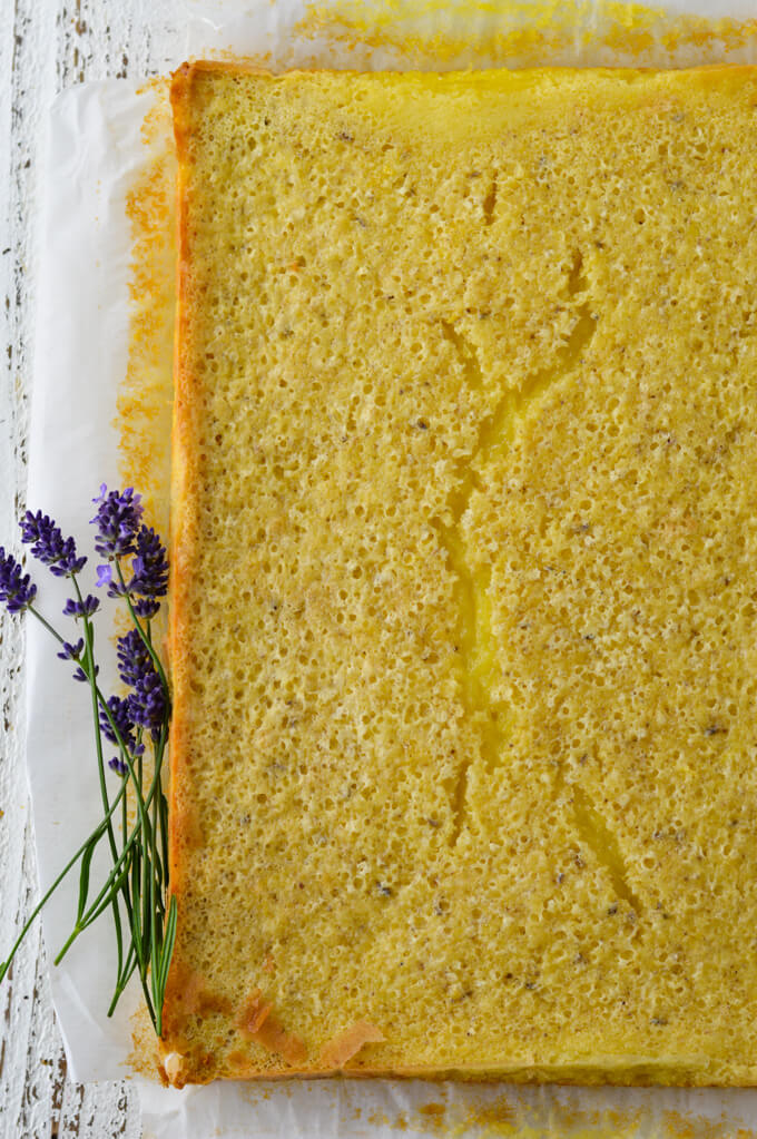 A baked whole sheet of lemon bars sitting on a sheet of parchment paper with sprigs of lavender beside it.