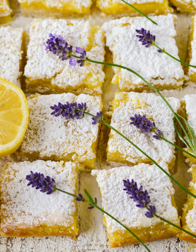 Cut lavender infused lemon bars with powdered sugar on top. Lavender sits on top of each bar with a lemon half in part of the photo.