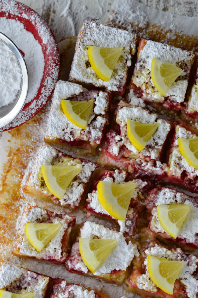 Baked strawberry lemon bars cut into squares with powdered sugar sprinkled on top and a little wedge of lemon sitting on top of each bar. A small red bowl with powdered sugar sits beside them.