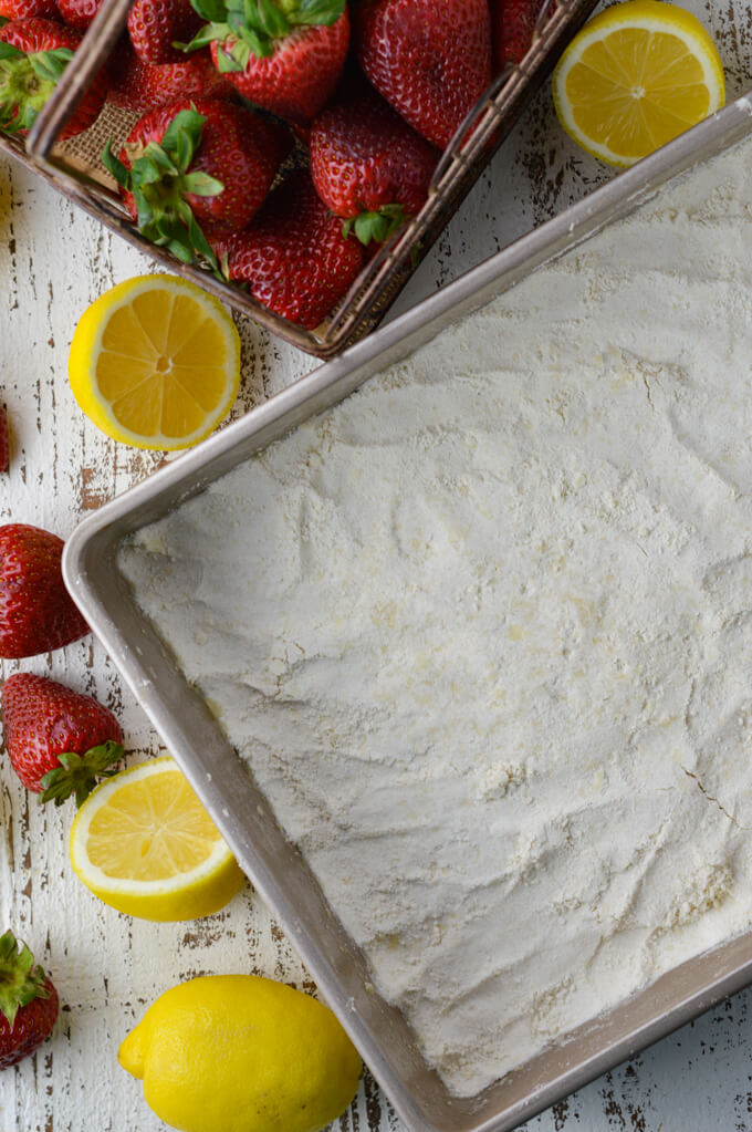 A pan of unbaked crust for strawberry lemon bars with whole strawberries and lemon halves scattered around it.
