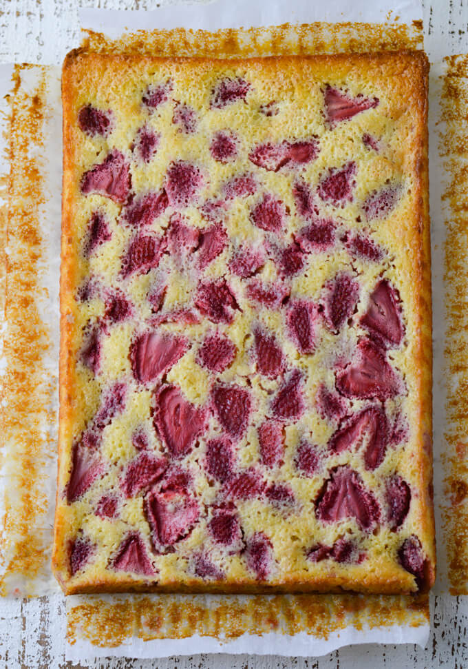 A sheet of baked strawberry lemon bars sitting on a piece of parchment paper that has crumbs around it.