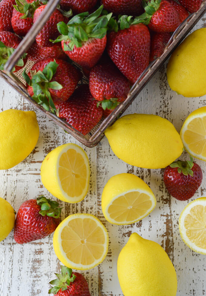 A basket of fresh strawberries on a white background. Whole lemons and half lemons with a few whole strawberries are scattered around in front.