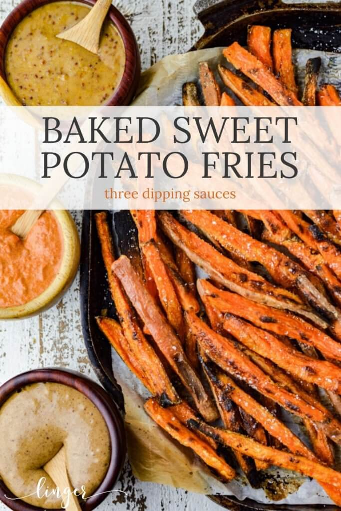 A baking sheet with parchment paper and baked sweet potato fries sit on it. Three dipping sauces sit next to the pan.