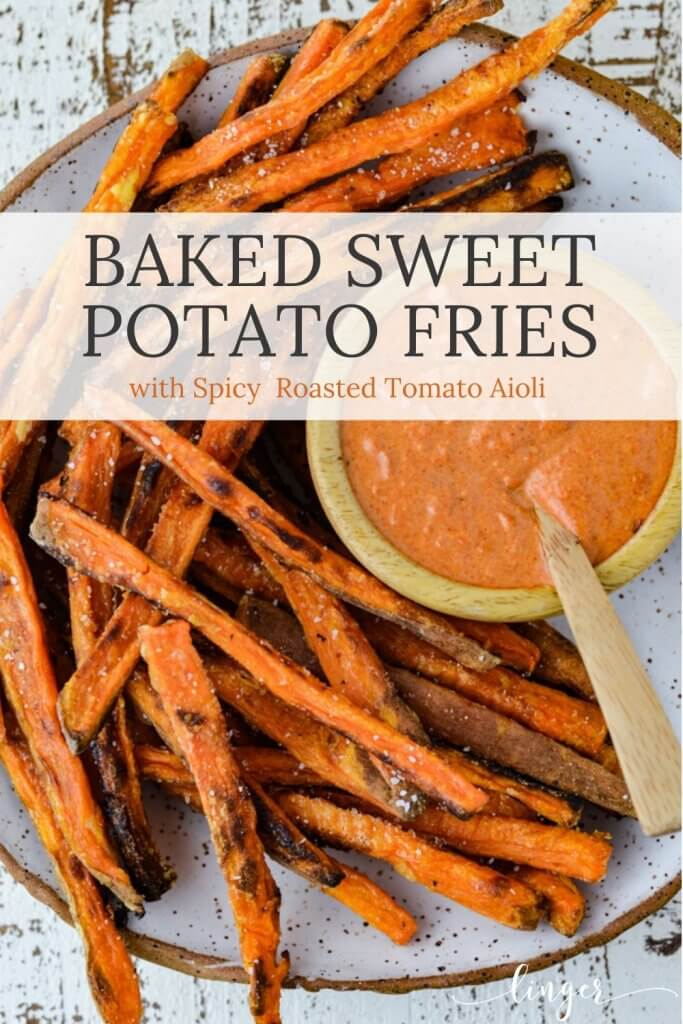 A plate of baked sweet potato fries with a roasted tomato aioli sits next to them.