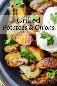 Grilled potatoes and onions in a blue bowl garnished with a dollop of sour cream and parsley.