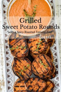Grilled sweet potato rounds sit on a white platter with a bowl of dipping sauce next to them.