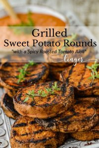 Grilled sweet potato rounds sit on a white platter with sprigs of thyme sitting on them. A bowl of dipping sauce sits in the background.