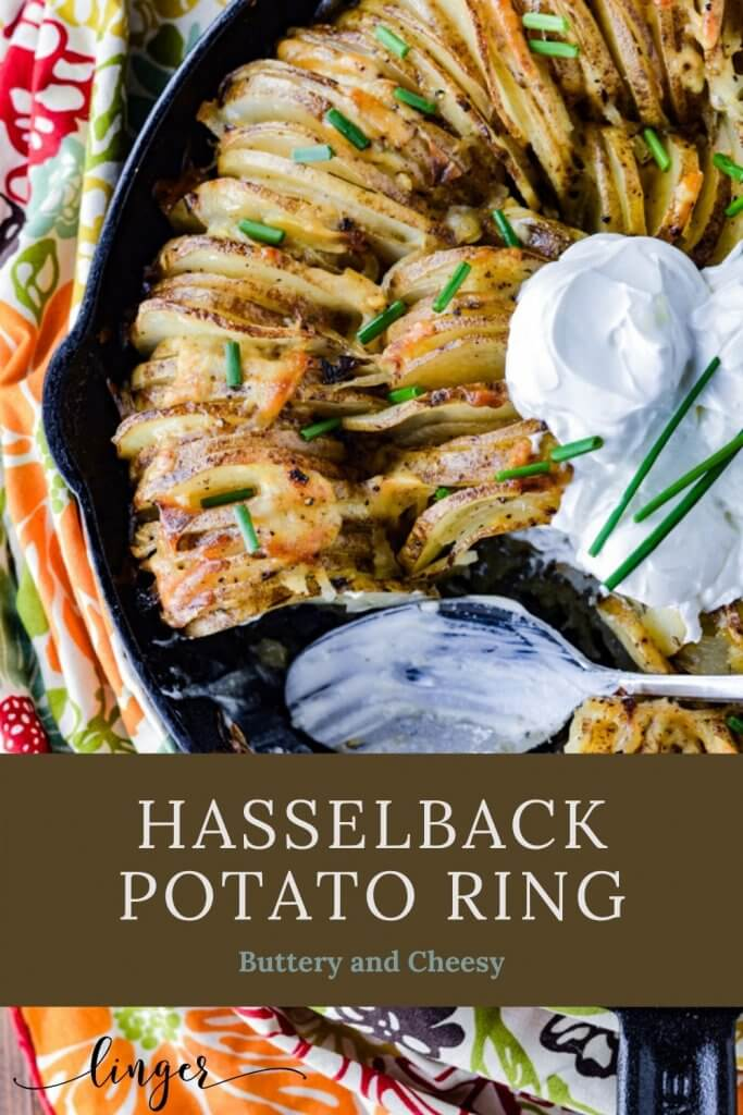 A hasselback potato ring in a cast iron skillet garnished with three dollops of sour cream and chopped chives. A colorful napkin sits beside the skillet. A spoonful has been taken out and the spoon with sour cream is still in the skillet.
