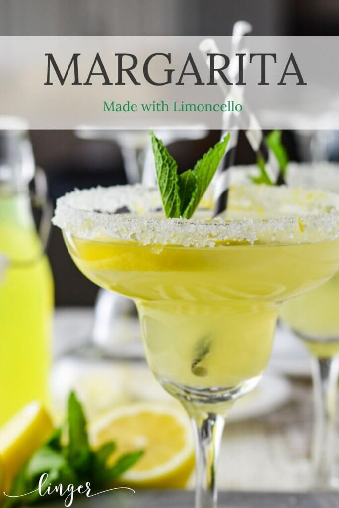 A front view of 2 limoncello margarita cocktails with a sugared rim and a garnish of fresh mint.