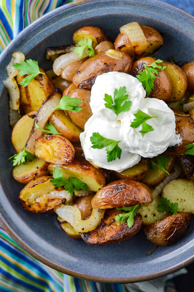 Grilled potatoes and onions with dollops of sour dream and garnished with parsley sitting in a blue bowl with a blue striped napkin sitting beside it.