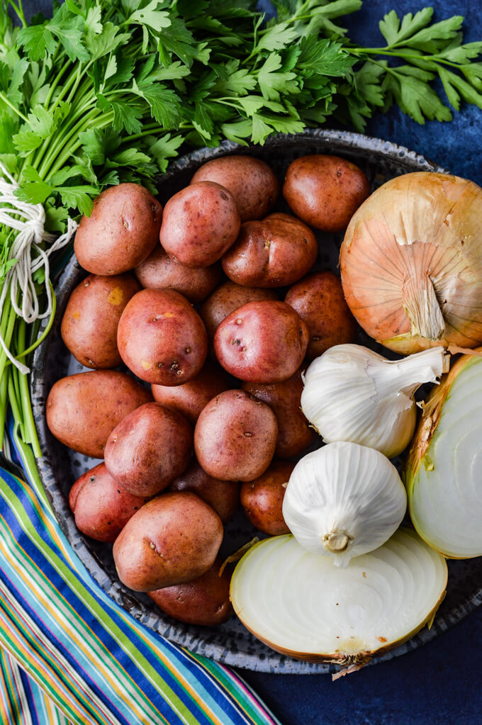 A bowl of small red potatoes, some onions and garlic and a bunch of parsley around the bowl.