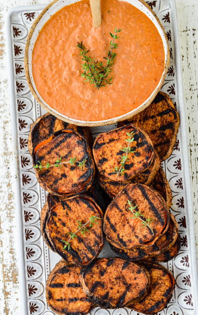 Grilled sweet potatoes sit on a white platter with a bowl of dipping sauce next to them.