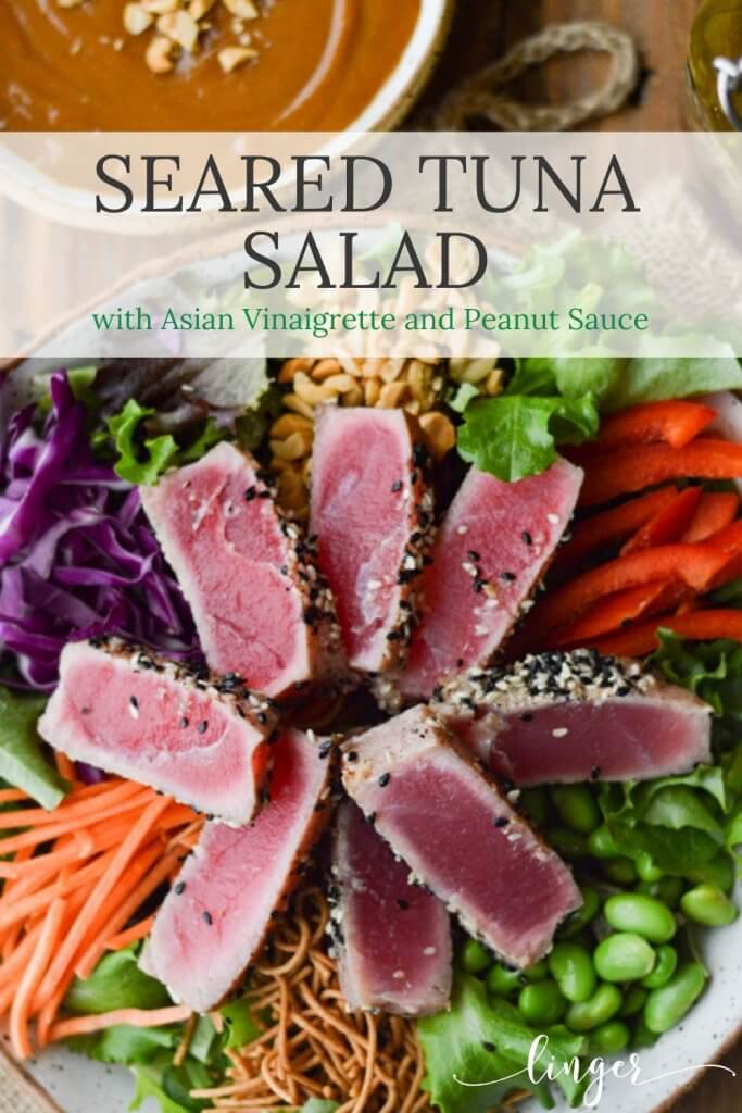 A bowl of salad with seared tuna, edamame, red cabbage, peanuts, red peppers and rice noodles.