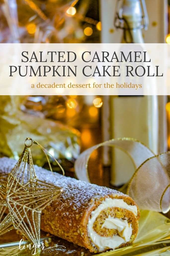 A pumpkin cake roll iced and rolled with caramel cream cheese filling sits on gold wrapping paper. A gold star ornament and white and gold ribbon lay around it with Christmas lights in the background.