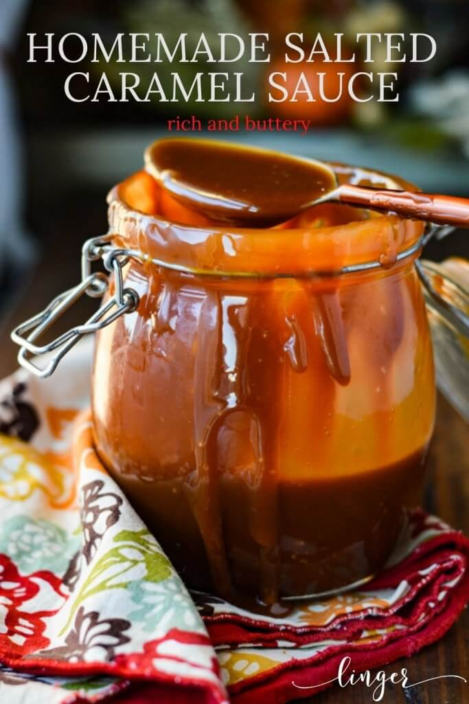 A messy jar of homemade caramel sauce sits on a colorful napkin with sauce dripping from the jar. A spoon of sauce sits on top the jar.