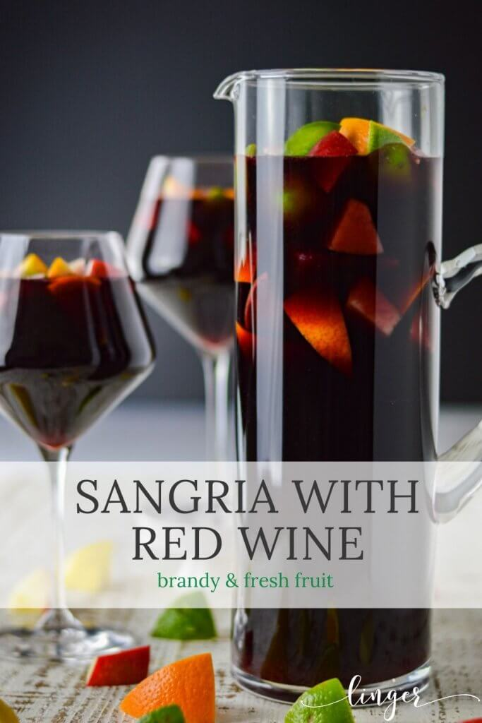 A pitcher of red wine sangria with chunks of fresh apples, oranges, lemons and limes. Two glasses filled with the sangria sit beside the pitcher. Chucks of the fresh fruit are scattered on the board below.