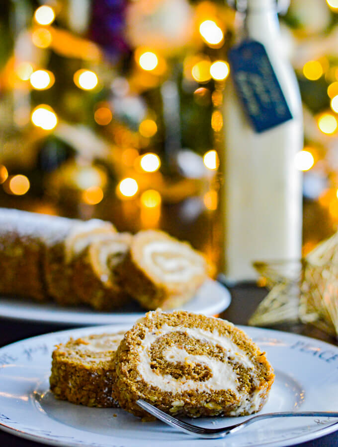 Two slices of pumpkin cake roll sit on a white plate with a fork. A plate of several slices and a jar of eggnog sits in the background. A Christmas tree with lights are blurred in the background.