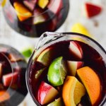 A photo from above of a pitcher of red wine sangria with chunks of fresh apples, oranges, lemons and limes. Two glasses filled with the sangria sit beside the pitcher. Chucks of the fresh fruit are scattered on the board below.