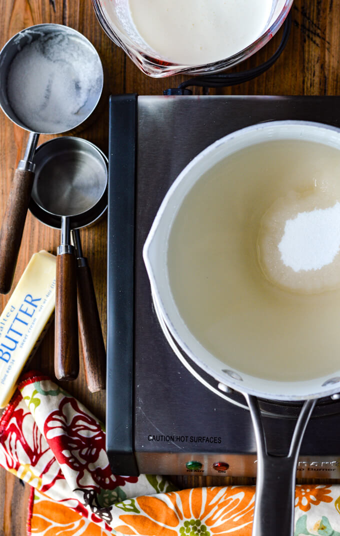 A pan of sugar and water sit on a portable stove top. Measuring cups, one filled with cream, a stick of butter and a colorful napkin sit next to the stove top.